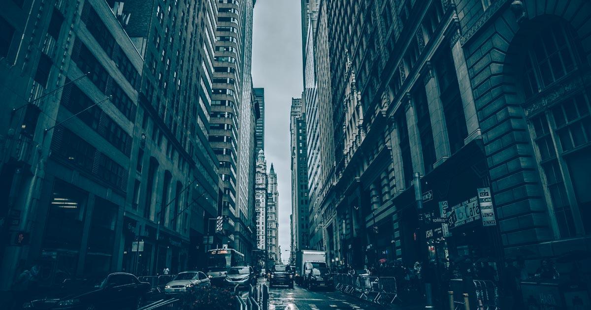 Imagem mostra uma rua de uma cidade cheias de carros e com prédios altos de ambos os lados