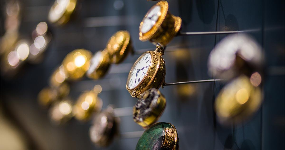 Vários relógios dourados presos a uma superfície e dispostos um ao lado do outro