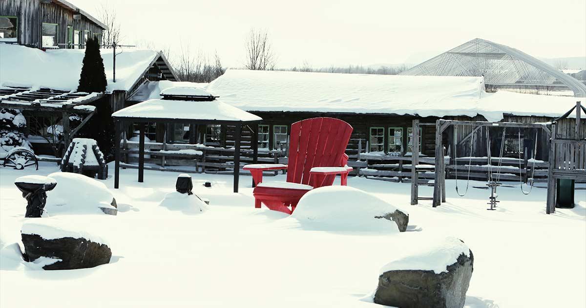 Cadeira de madeira vermelha em um quintal coberto de neve