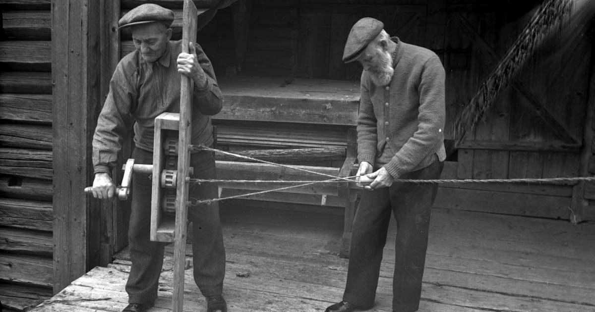 Two elderly people weaving wire in an old machine.