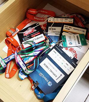 Interior de uma gaveta com vários crachás de eventos de desenvolvimento web e design