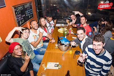 Organização do evento Front in Sampa e convidados sentados em uma mesa de um bar acenando para a foto