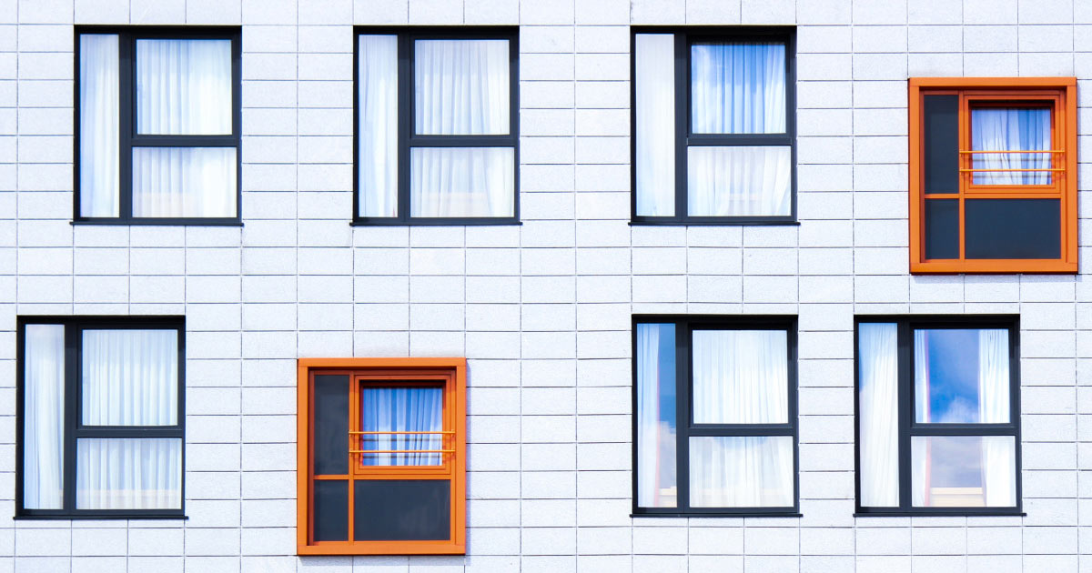 White wall of a house with several windows with details in gray, and two of them in orange