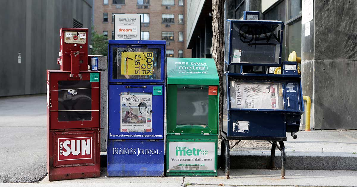 Photo shows four newspaper boxes, probably Americans in residential neighborhood