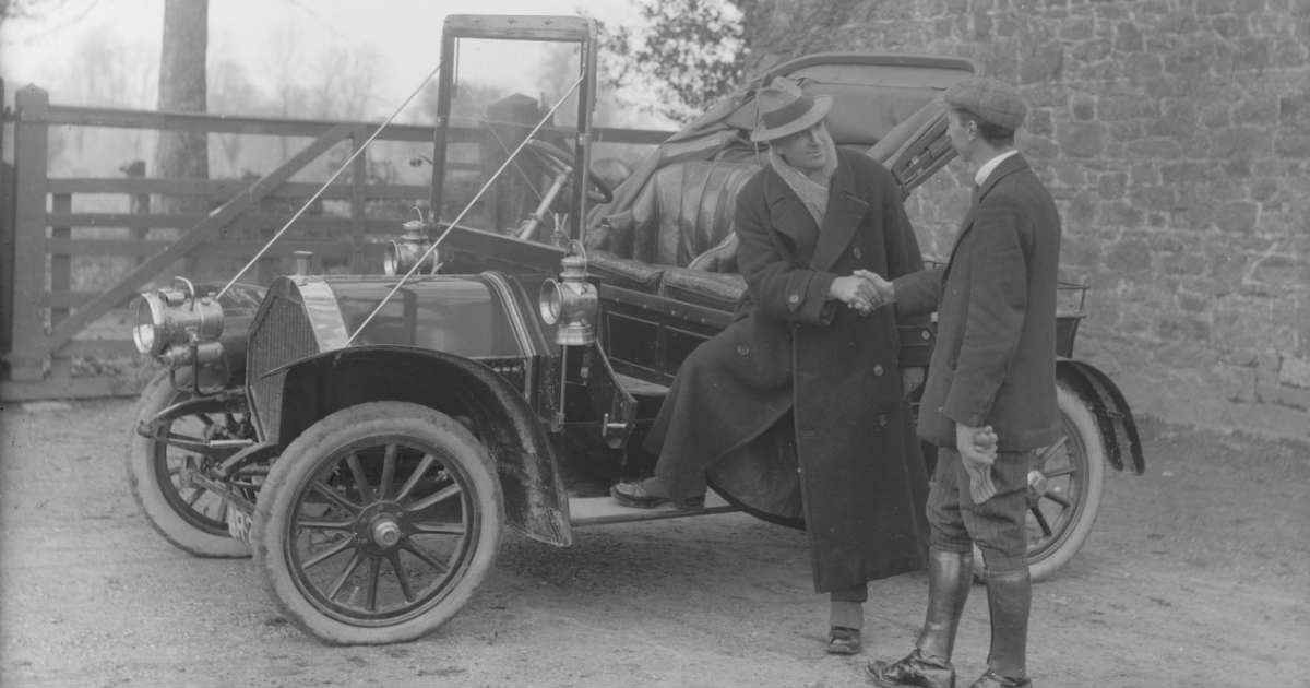 Two men shaking hands in front of an old car (probably the 20 or 30 decade)