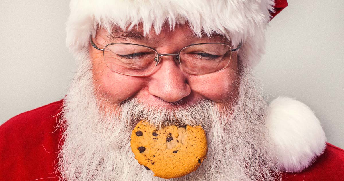 Image of a man costumed Santa Claus with a cookie in his mouth