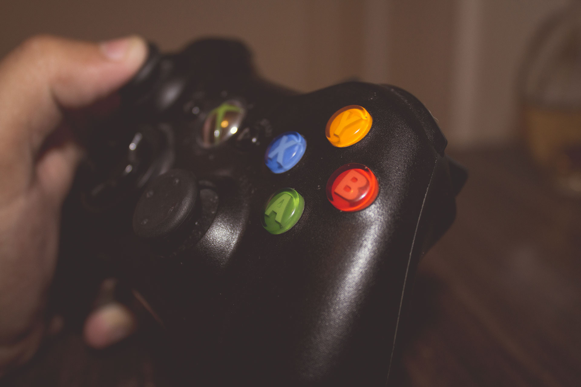 Imagem mostra um controle de xbox segurado por uma pessoa
