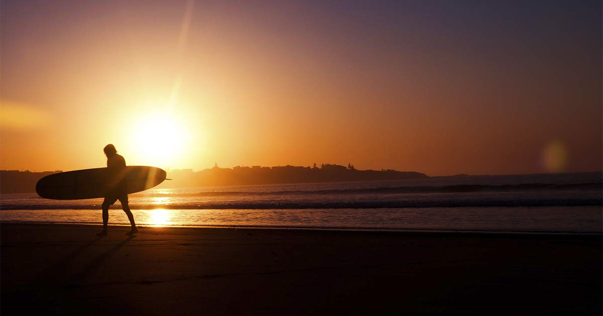 Surfista caminhando em uma praia segurando uma prancha com o por do sol ao fundo