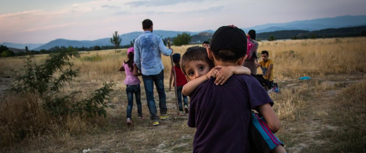A young Syrian refugee carries his brother near Eidomeni, Greece.